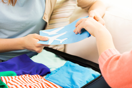 luggage travel: tourism, vacation, luggage and people concept - close up of women with airplane tickets and clothes in travel bag at home