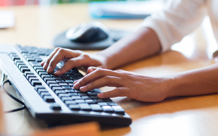 keyboards: business, education, programming, people and technology concept - close up of african american female hands typing on keyboard
