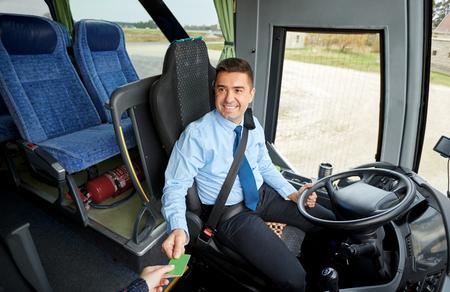 chofer: transporte, turismo, viaje por carretera y la gente concepto - sonriendo conductor del autobús teniendo billete o tarjeta de plástico a partir de pasajeros Foto de archivo
