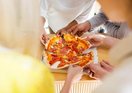 Voedsel, lunch en mensenconcept - sluit omhoog van vrienden of mensen die pizza eten Stockfoto - 60805442
