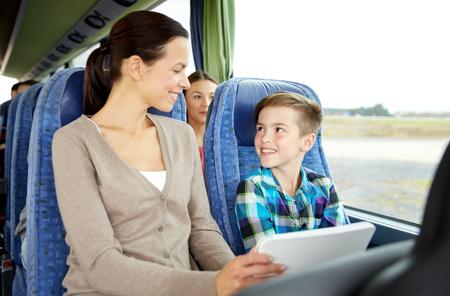 viaje familia: los viajes, el turismo, la familia, la tecnología y el concepto de la gente - Madre e hijo felices con el ordenador Tablet PC que se sientan en los viajes de autobús Foto de archivo