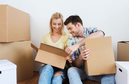 to unpack: home, people, repair and real estate concept - smiling couple with many cardboard boxes moving to new place Stock Photo