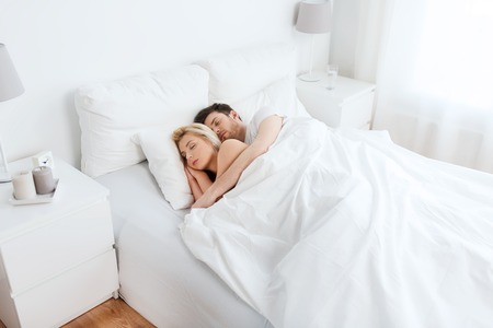 people, rest and relationships concept - happy couple sleeping in bed at home Stock Photo