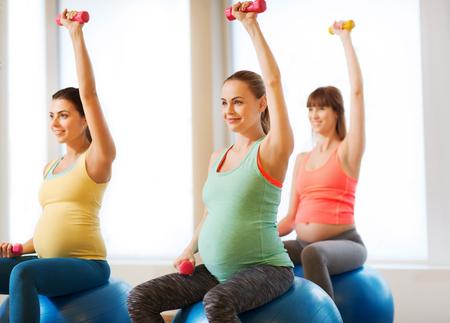 zwangerschap, sport, fitness, mensen en een gezonde levensstijl concept - groep van gelukkige zwangere vrouwen met halters te oefenen op de bal in de sportschool Stockfoto