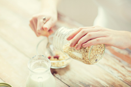 groat: food, healthy eating, people and diet concept - close up of woman eating muesli with milk for breakfast Stock Photo