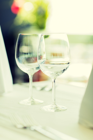 set up: glassware and objects concept - close up of two wine glasses on restaurant table
