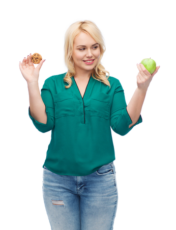 eating food: healthy eating, junk food, diet and choice people concept - smiling woman choosing between apple and cookie Stock Photo