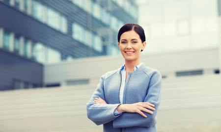office building: business and people concept - young smiling businesswoman over office building Stock Photo