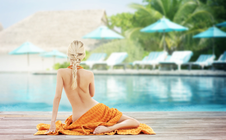people, travel, tourism, summer vacation and people concept - woman with orange towel from back over exotic hotel resort beach with swimming pool and sunbeds background photo