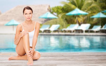 piernas mujer: la gente, la belleza y las vacaciones de verano concepto - mujer joven en ropa interior de algodón tocando sus piernas sobre exótica playa del complejo de hotel con piscina y tumbonas fondo