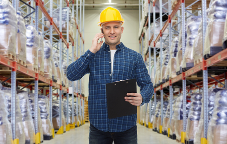 men talking: wholesale, logistic, business, export and people concept - smiling businessman with clipboard calling on smartphone over warehouse background