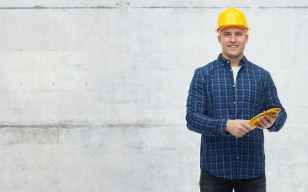 Hormigón: repair, building, construction, people and maintenance concept - smiling man in helmet with gloves over gray concrete wall background