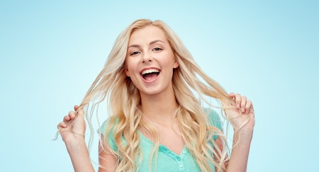 young woman smiling: emotions, expressions, hairstyle and people concept - smiling young woman or teenage girl holding her strand of hair over blue background
