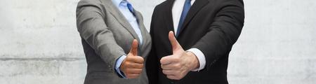 zaken, mensen en gebaarconcept - sluit omhoog van zakenman en onderneemster die duimen over grijze concrete muurachtergrond tonen Stockfoto