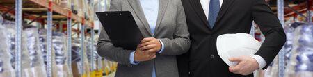 negocios internacionales: al por mayor, logística, comercio internacional, la exportación y la gente concepto - cerca del hombre y de la mujer en el almacén con el sombrero duro y el sujetapapeles sobre el fondo del almacén Foto de archivo