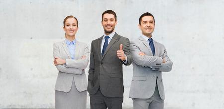 negocio, las personas, el trabajo en equipo, el éxito y el concepto gesto - personas felices mostrando los pulgares para arriba Foto de archivo