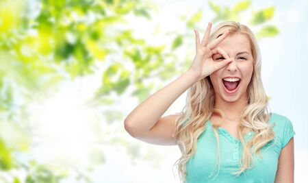 green eyes: fun, emotions, expressions, summer and people concept - smiling young woman or teenage girl making ok hand gesture over green natural background