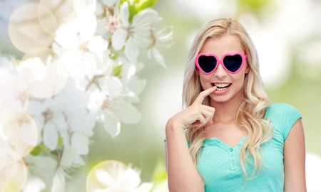 guessing: emotions, expressions, summer and people concept - smiling young woman or teenage girl in heart shape sunglasses over natural spring cherry blossom background