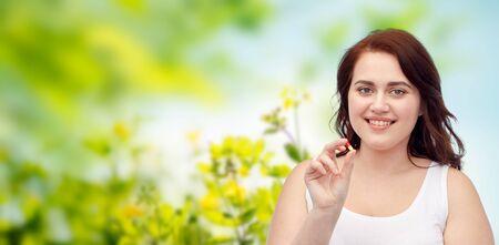 gewichtsverlies, dieet, afslanken, medicijnen en mensen concept - happy plus size vrouw in ondergoed met pil over groene natuurlijke kruiden achtergrond