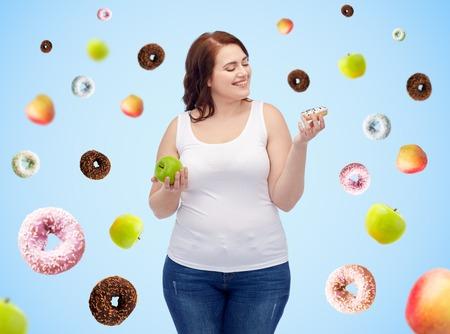 comida chatarra: alimentación saludable, la comida chatarra, la dieta y el concepto de la gente elección - sonriente mujer de talla grande elige entre la manzana y la rosquilla sobre fondo azul Foto de archivo
