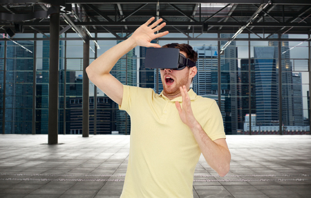 entertainment background: 3d technology, virtual reality, entertainment and people concept - scared young man with virtual reality headset or 3d glasses playing game over empty industrial room and city panorama background Stock Photo