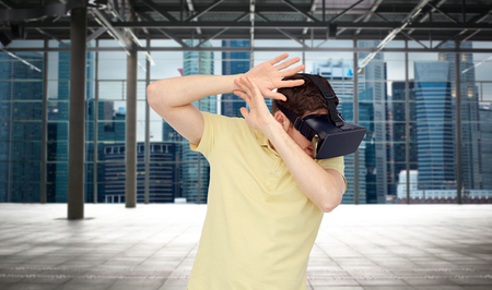 mediated: 3d technology, virtual reality, entertainment and people concept - scared young man with virtual reality headset playing game over empty industrial room and city panorama background