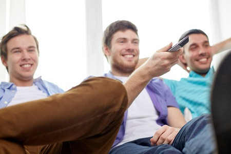 entertainment concept: friendship, sports, people and entertainment concept - happy male friends with remote control watching tv at home Stock Photo