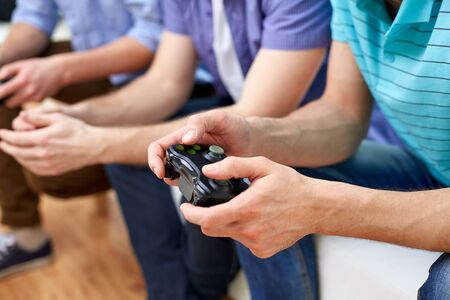 out of control: friendship, technology, games and home concept - close up of male friends playing video games at home