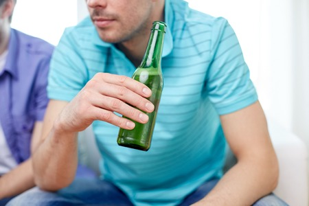 alcohols: leisure, people and alcohol concept - close up of man drinking beer at home Stock Photo
