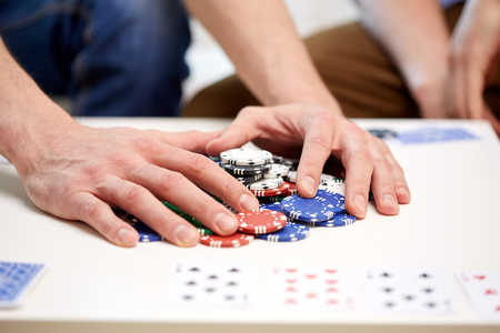 bet: leisure, games, gambling and entertainment - close up of male hands with casino chips and playing cards making bet or taking win at home