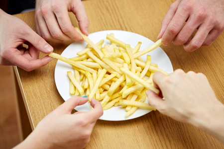 fast food, unhealthy eating, people and junk-food - close up of hands taking french fries from plate on table