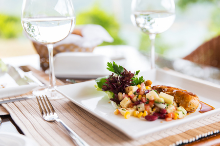 meat: food, cooking and eating concept - close up of meat dish with garnish and water glasses on table at restaurant or home Stock Photo