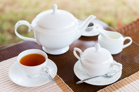 teatime: teatime, drink and object concept - close up of tea service on table at restaurant or teahouse