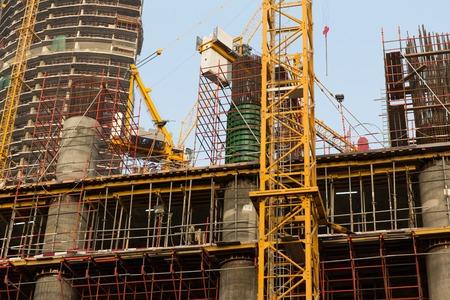 la construcción, el desarrollo, la arquitectura, la industria y el concepto de ingeniería - construcción de rascacielos en la ciudad de Dubai Foto de archivo