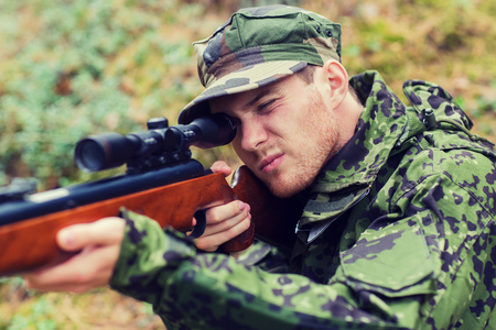 infantryman: hunting, war, army and people concept - young soldier, ranger or hunter with gun aiming and shooting in forest