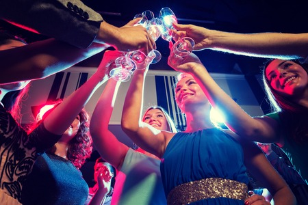people having fun: party, holidays, celebration, nightlife and people concept - smiling friends with glasses of champagne in club