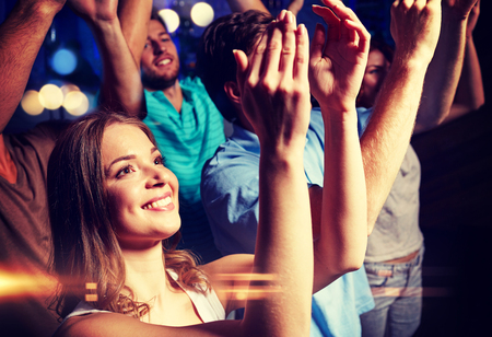 applauding: party, holidays, celebration, nightlife and people concept - smiling friends applauding at concert in club