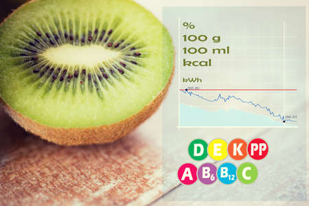 fruits, diet, food and objects concept - close up of ripe kiwi slice on table with calories and vitamin chart Stock Photo