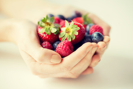 berries: healthy eating, dieting, vegetarian food and people concept - close up of woman hands holding berries at home