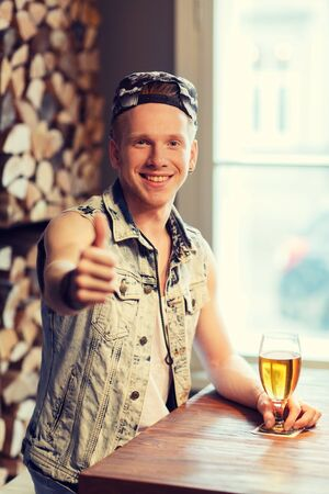 people, drinks, alcohol, gesture and leisure concept - happy young man drinking beer and showing thumbs up at bar or pub Stock Photo