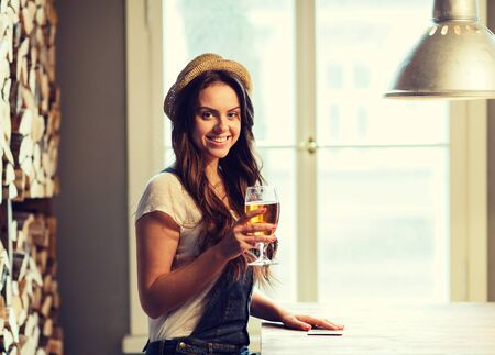 nonalcoholic beer: people, drinks, alcohol and leisure concept - happy young redhead woman drinking beer at bar or pub Stock Photo