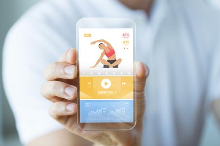 mensen, technologie, sport en fitness concept - sluit omhoog van mannelijke hand met smartphone met sportentoepassing op het scherm Stockfoto