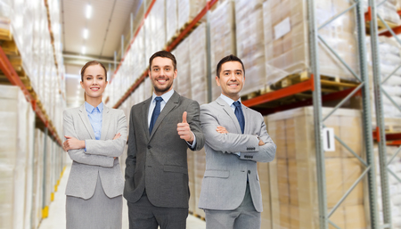 wholesale, logistic, business, export and people concept - happy man in suit and tie showing thumbs up gesture over warehouse background