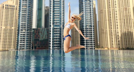 young girl smiling: people, travel, tourism, summer vacation and holidays concept - happy young woman jumping over dubai city infinity edge pool background