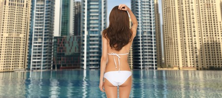 people, summer holidays, travel, tourism and vacation concept - woman in bikini swimsuit from back over dubai city and infinity edge pool background photo