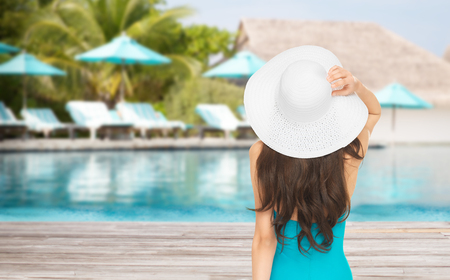 people, summer holidays, travel, tourism and vacation concept - woman in swimsuit and sun hat from back over exotic hotel resort beach with swimming pool and sunbeds background photo