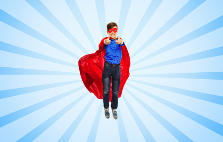 air movement: happiness, freedom, childhood, movement and people concept - boy in red super hero cape and mask flying in air and showing thumbs up over blue burst rays background