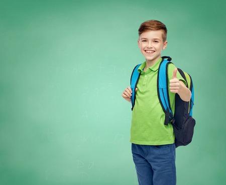 kinderjaren, onderwijs en mensenconcept - gelukkige glimlachende studentenjongen met schooltas over de groene achtergrond van het schoolbord