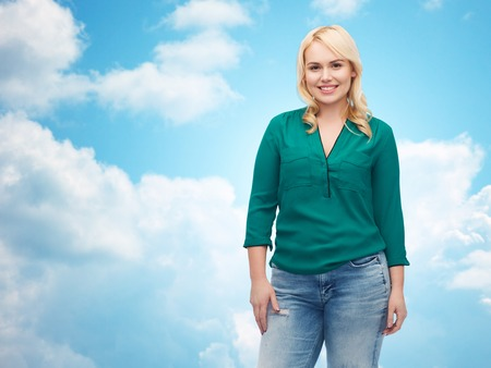 hispanic girl: female, gender, portrait, plus size and people concept - smiling young woman in shirt and jeans over blue sky and clouds background Stock Photo