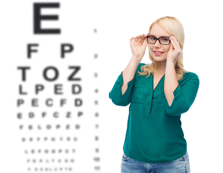 overweight students: vision, ophthalmology, optics, health care and people concept - smiling young woman with eyeglasses over eye chart background Stock Photo